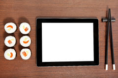 Tablet on a table near sushi Stock Photos