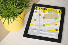 Tablet taxi app over a table with plant Stock Photo