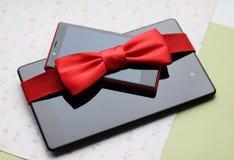 Tablet, telefoon met rode boog, gift Stock Foto's
