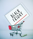 Tablet with text black friday in a shopping cart Stock Photos