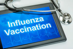 Tablet with the text Influenza Vaccination. On the display Stock Photo