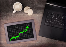 Tablet touch computer gadget on wooden table, graph positive Stock Photo