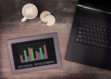 Tablet touch computer gadget on wooden table, graph Royalty Free Stock Photos