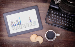 Tablet touch computer gadget on wooden table, graph Royalty Free Stock Images