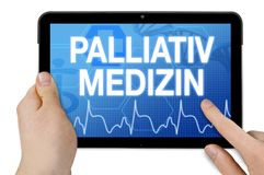 Tablet with touchscreen and the german word for palliative medicine and care royalty free stock photos