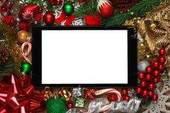 Tablet umgeben mit Weihnachtsdekorationen Lizenzfreie Stockfotos
