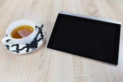 Tablet und eine Tasse Tee stockfotos