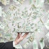 Tablet und fallender Dollar Stockfotos