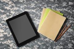 Tablet und Schreibhefte auf Tarnungshintergrund Lizenzfreies Stockfoto