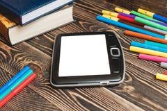 Tablet und Schulbedarf auf hölzernem Hintergrund Stockfotografie