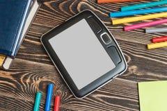Tablet und Schulbedarf auf hölzernem Hintergrund Stockfoto