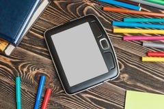 Tablet und Schulbedarf auf hölzernem Hintergrund Lizenzfreie Stockfotos