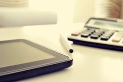 Tablet und Taschenrechner auf einem Schreibtisch Stockfotografie