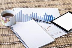 Tablet und Teeschale mit Finanzdokumenten Lizenzfreie Stockbilder