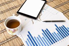 Tablet und Teeschale mit Finanzdokumenten Stockbilder