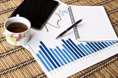 Tablet und Teeschale mit Finanzdokumenten Stockbild