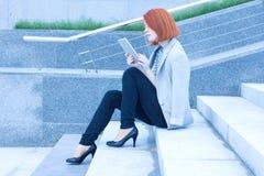Tablet van de bedrijfs de aantrekkelijke vrouwenlezing zorgvuldig Stock Foto's