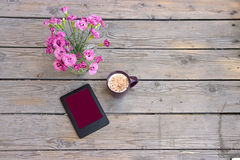 The tablet , a vase of flowers and a cup of coffee with milk Stock Photo