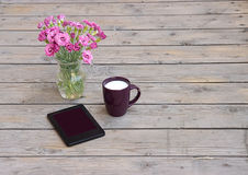 The tablet , a vase of flowers and a cup of coffee with milk Royalty Free Stock Images