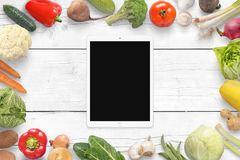 Tablet and vegetables on wihite wooden desk. Top view.  royalty free stock photo