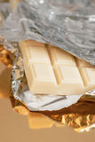 Tablet of white chocolate beginning to show for the silver foil Royalty Free Stock Images