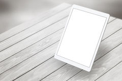 Tablet with white  screen on wooden desk. Isometric view. Royalty Free Stock Images