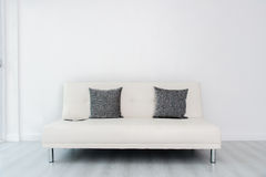 Tablet on white sofa bed in white room Stock Image