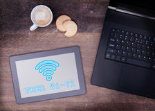 Tablet with Wi-Fi connection on a wooden desk. Vintage setting stock photography