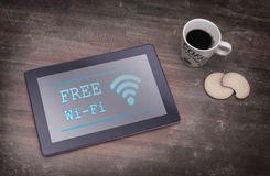Tablet with Wi-Fi connection on a wooden desk. Vintage setting royalty free stock images