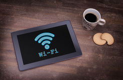 Tablet with Wi-Fi connection on a wooden desk. Vintage setting stock photos