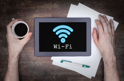 Tablet with Wi-Fi connection on a wooden desk. Vintage setting royalty free stock photography