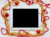 Tablet on winter holiday background. Christmas decorations Stock Photo