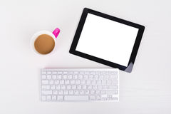 Tablet, wireless keyboard and cup of coffee on white table Royalty Free Stock Image