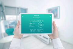 Free Tablet With The Positive Corona Virus Findings In The Hands Of A Nurse In A Hospital Room Stock Photo - 176012260