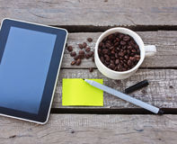 Tablet on wood background. Coffee beans and tablet on wood background Royalty Free Stock Photo