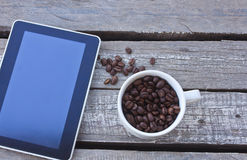 Tablet on wood background. Coffee beans and tablet on wood background Royalty Free Stock Image