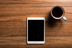 Tablet on wood with coffee Stock Image