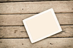 Tablet on wooden background. Royalty Free Stock Photos