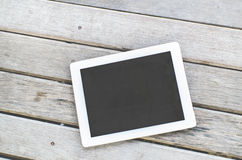 Tablet on wooden background. Royalty Free Stock Photo