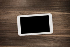 Tablet on wooden desk table. Royalty Free Stock Photo
