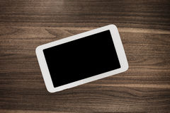 Tablet on wooden desk table. Stock Photos