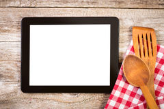 Tablet on wooden surface and serving spoons. Royalty Free Stock Photo