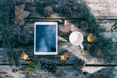 Tablet on a wooden table with coffee and pines outdoor royalty free stock images
