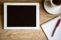 Tablet on wooden table. Tablet with notebook on wooden table, top view royalty free stock image