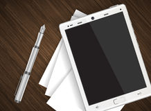 Tablet on wooden table with paper Stock Photography