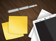 Tablet on wooden table with yellow stick notes Royalty Free Stock Image