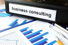 Tablet with word business consulting  and graphs. Royalty Free Stock Photo