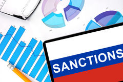 Tablet with word sanctions on the Russian flag. And graphs. Concept photo stock photography