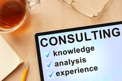 Tablet with words consulting. Business and management concept Royalty Free Stock Photo