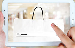 Tablet with www. on search bar over shopping bag and blur store Royalty Free Stock Photo